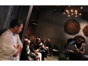 """Ryan Carson, left, listens as his sister Denise, right, reads from her new book """"Parting Ways: New Rituals and Celebrations of Life's Passing."""" Ryan is the chef at AnQi Restaurant in Costa Mesa where the book release gathering was held. CHRISTINE COTTER, FOR THE ORANGE COUNTY REGISTER"""